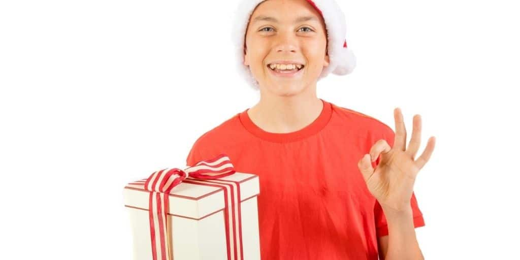 tween boy wearing Santa hat with cheap stocking filler for boy gift