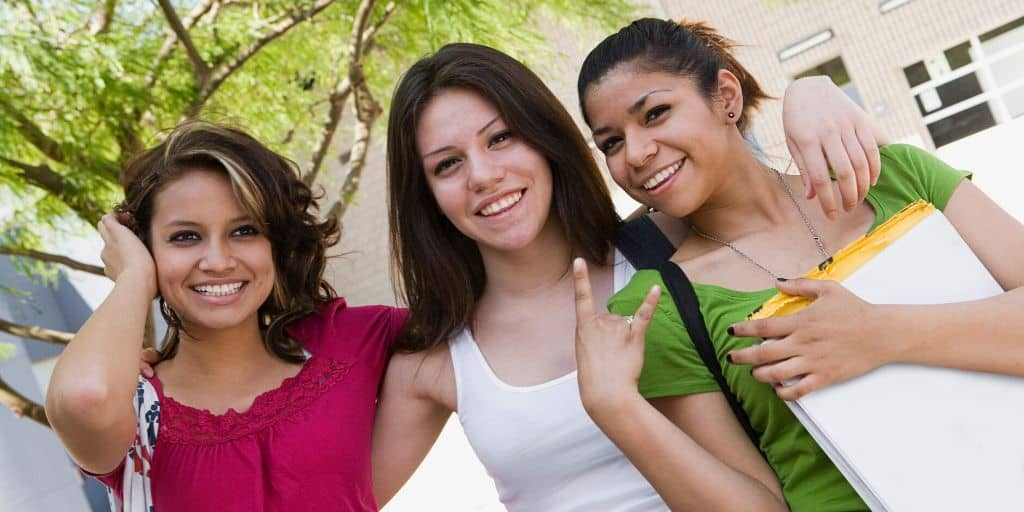 three smiling teenage girls wondering what are good goals for a teenager?