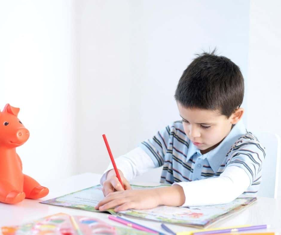 young boy with piggy bank, working on free fun money game for 2nd graders