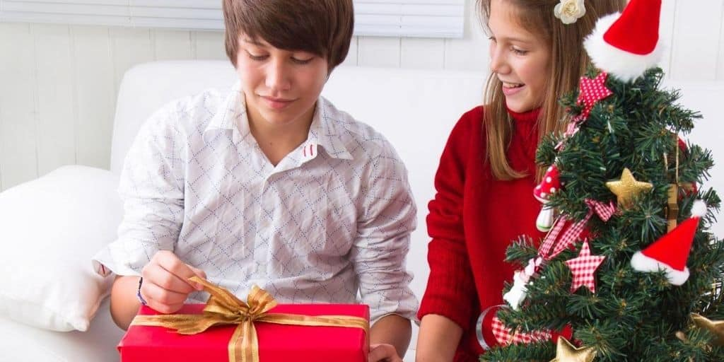 teenage guy smiling, opening up Christmas gift next to teen girl and Christmas tree