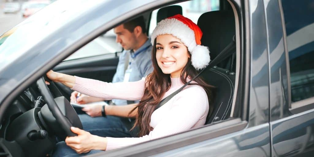 teen girl driver with Santa hat on, trying out stocking stuffers for teenagers she got Christmas morning