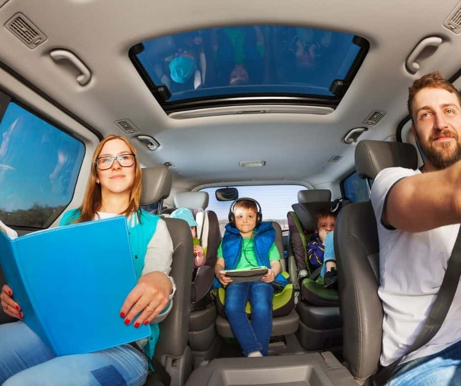 family of five (2 parents, 3 kids) that picked kids up from school and are doing homework in the car