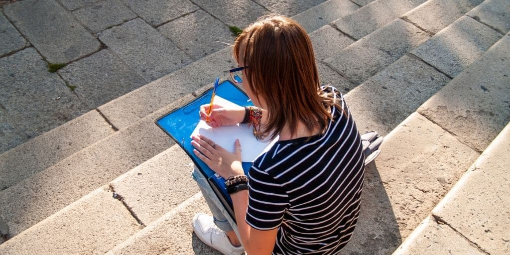 teen girl sitting on school steps with after school schedule at home on clipboard, writing
