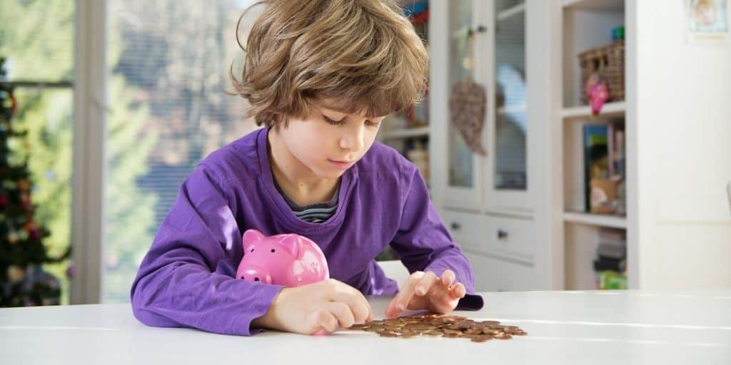 kid boy counting money with piggy bank, teaching budget for kids