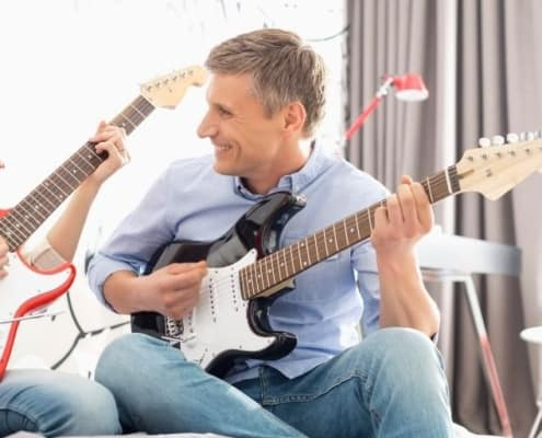 father playing guitar with teenage daughter as a family activity with teen