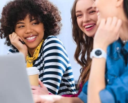 three teenage girls sitting at desk with laptop, smiling about gifts for teenage girls