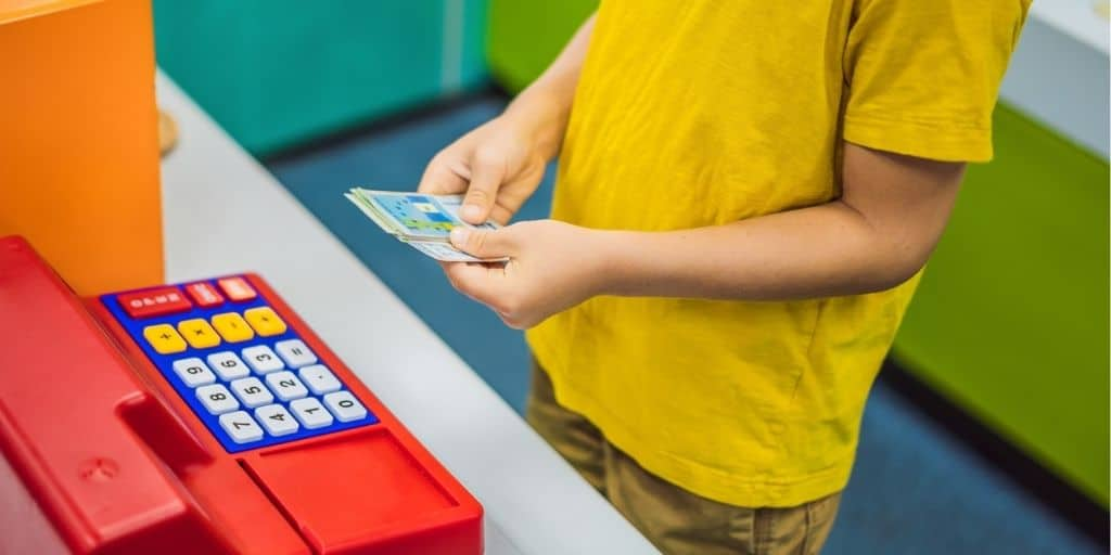 boy kid playing with printable play money for kids and play cash register