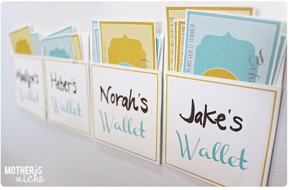 screenshot of free printable reward bucks system on wall, with bank envelopes for each child