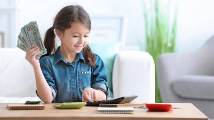 young girl with money in hand, calculator, learning money management for kids