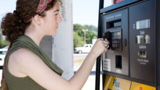 teenager using a debt card for kids at the gas pump