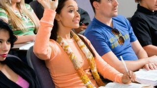row of high school students with girl in orange shirt raising hand