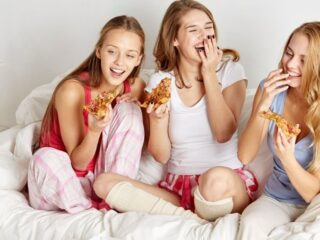 three teen girls laughing on bed with pizza doing 100 things to do at a sleepover at home
