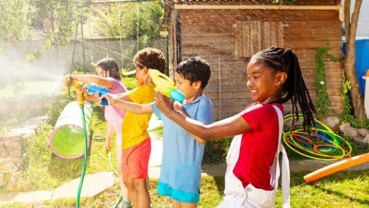 four kids in line having fun with water guns out in backyard