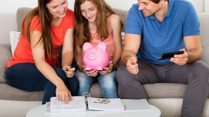 teen girl with piggy bank talking about why she should save money with parents on couch
