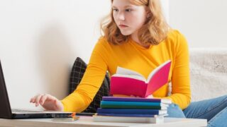 high school student girl with orange shirt reading red business book