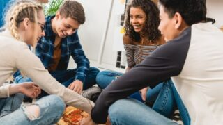 group of teens around a pizza, having a good time