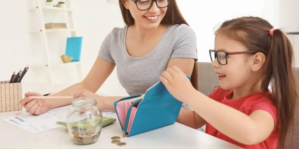 kid putting money into a wallet next to mother, who's using bank worksheet pdfs to teach her banking