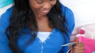 smiling teen girl holding best debit card for kids