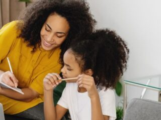 mother with daughter at desk smiling, identifying needs and wants on a worksheet they're working on