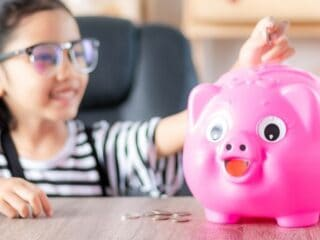 girl kid putting allowance for kids money into pink piggy bank