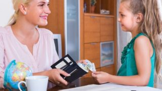 mother with wallet handing appropriate amount of allowance over to young daughter, smiling