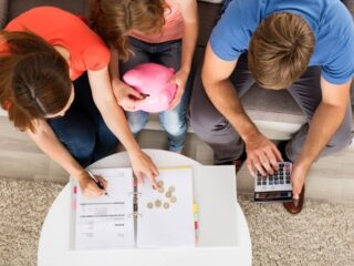 young teen girl with mom and dad working on money management skills with calculator and piggy bank at coffee table