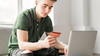teen boy with orange credit card at laptop, smiling