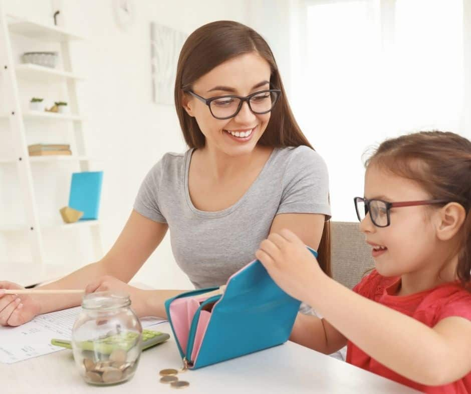 mother with preschool daughter, both smiling, playing with a wallet and calculator while educating child on money