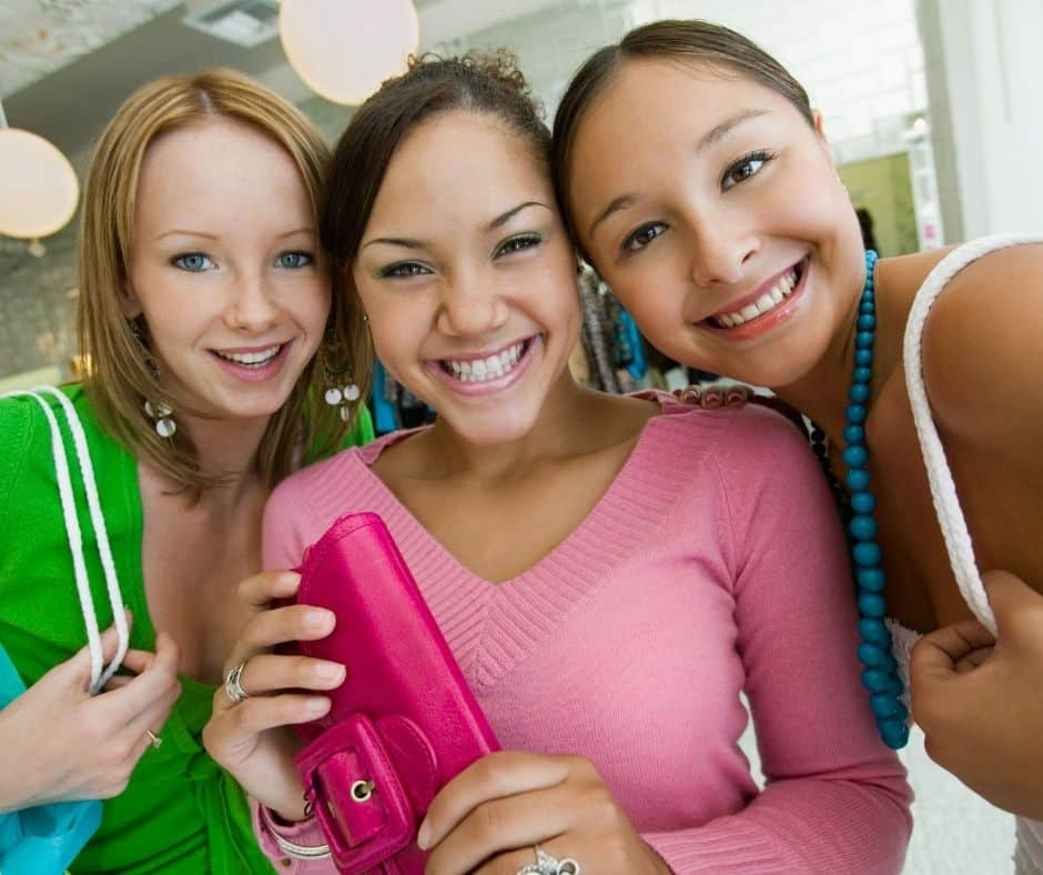 three teen girls hanging out at the mall with wallets and purses, smiling into the camera
