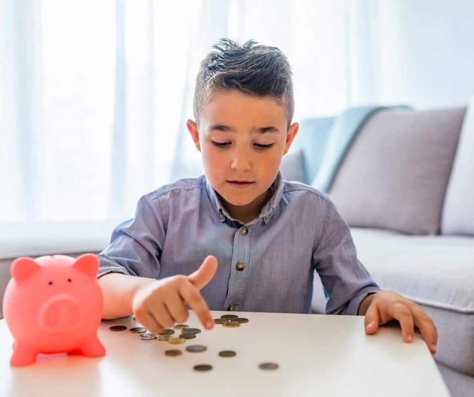 young boy with pink piggy bank, counting out his money