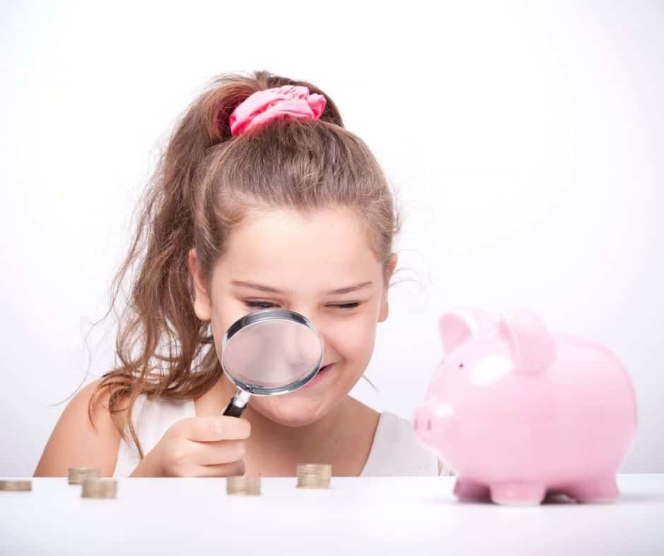 tween girl with magnifying glass looking at piles of coins, next to piggybank, smiling