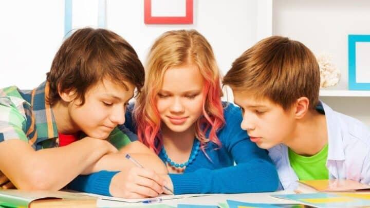 three older kids at desk writing business plan