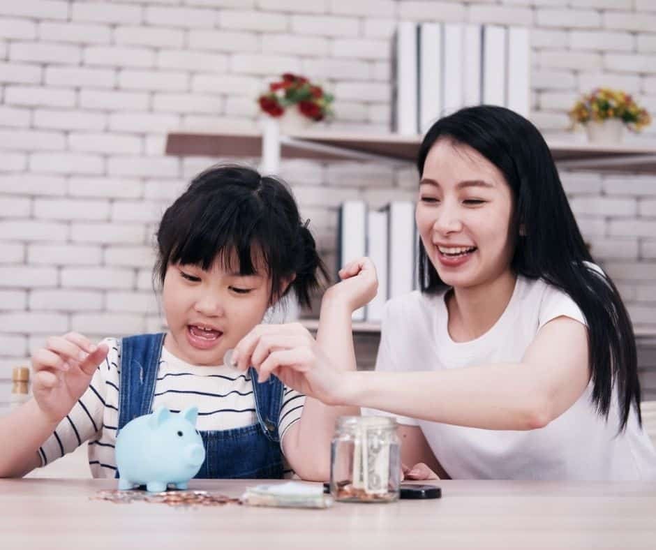 mother helping preschool daughter count coins in her blue piggybank, both having fun learning about money concepts