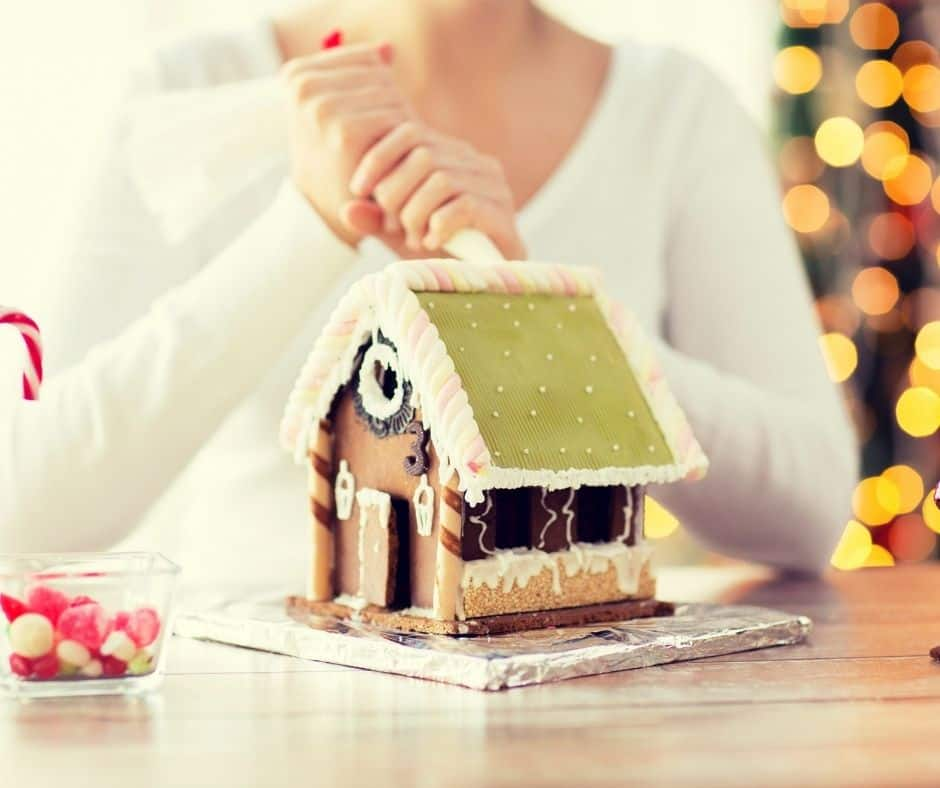 teen decorating gingerbread house with green roof, black sides, and white frosting