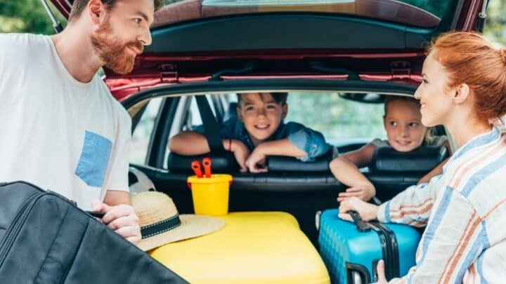 parents packing up trunk with two kids looking on, readying to survive a family road trip