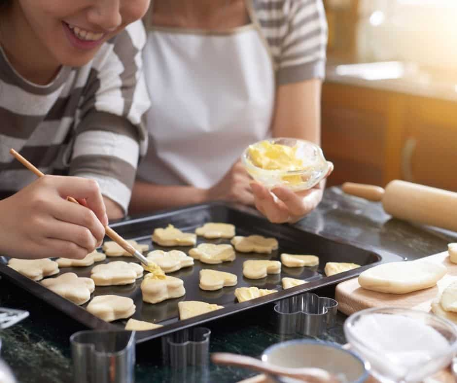 teen working with parent to decorate pan of sugar cookies