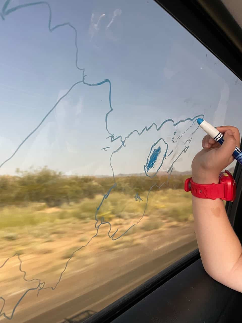 hand of 4-year-old drawing on window with window paint markers