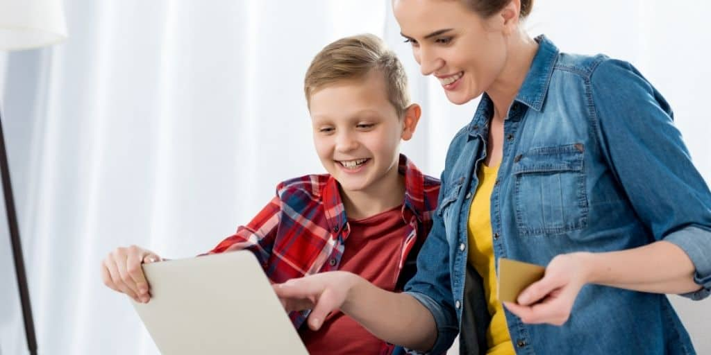 mom with tween son on computer, using goalsetter cashola debit card to make online purchase