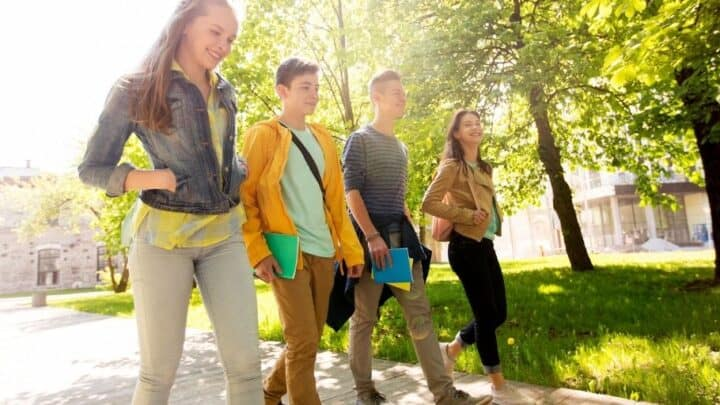 group of high school students in fall walking down walkway with smiles