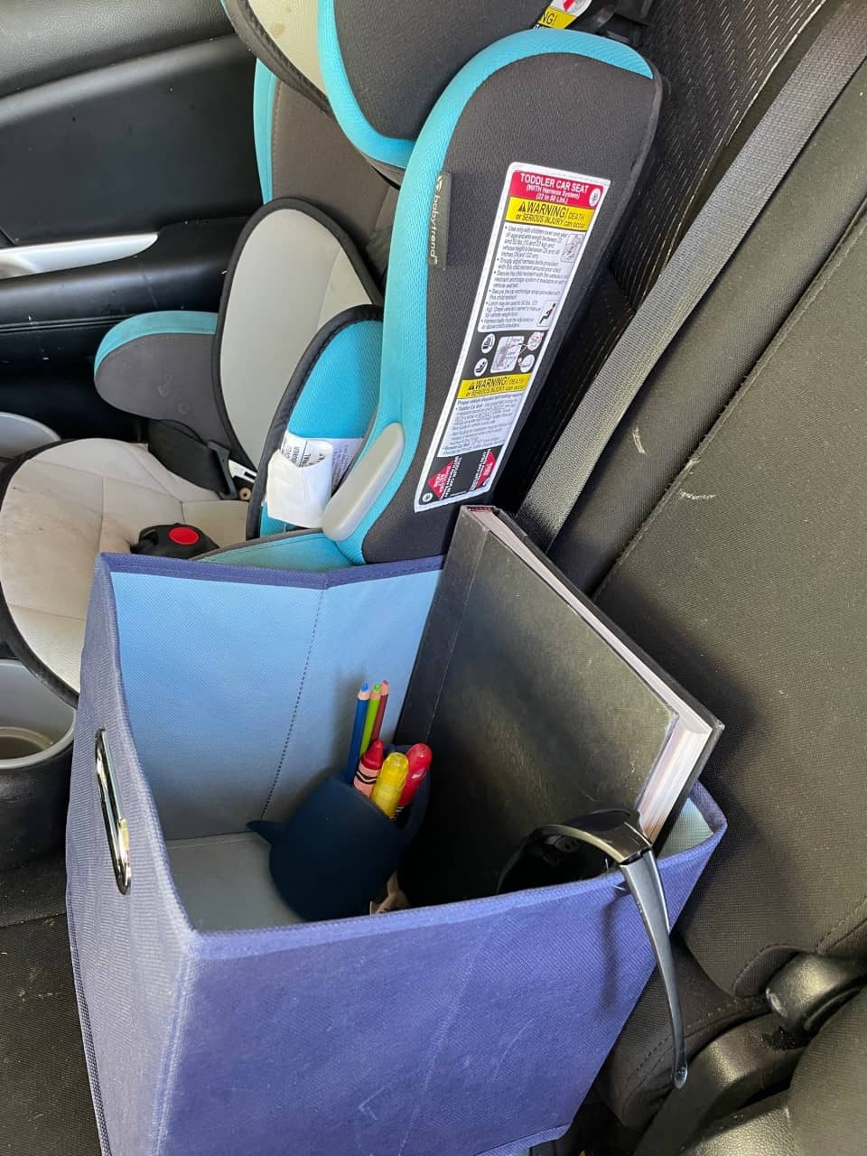 cloth bin next to child seat with sunglasses, rubber shark toothbrush holder with window paint markers and crayons, and book