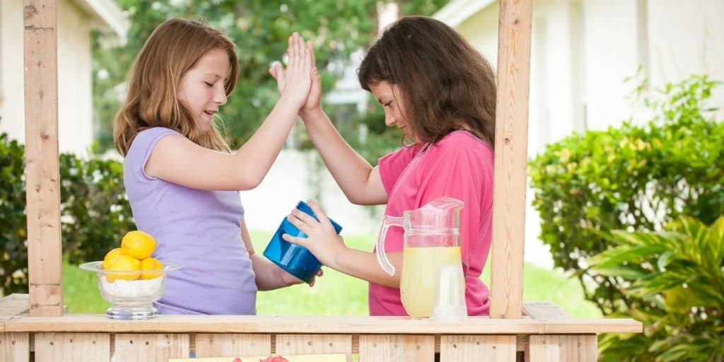 two kids slapping each other five, looking in money jar at lemonade stand