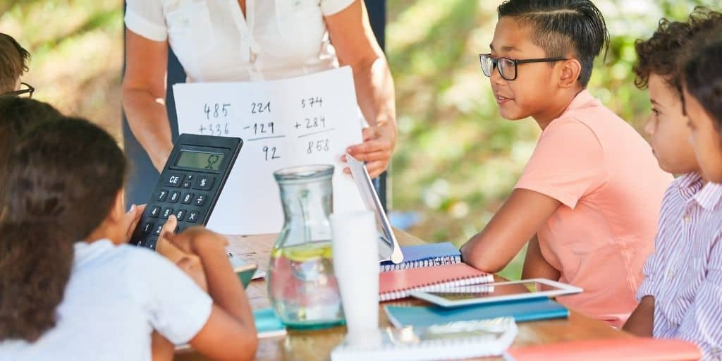 group of tweens with teacher at end of table, calculating lemonade stand math