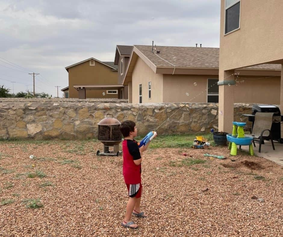 5 year old using a water gun to spray down bubbles floating in the air