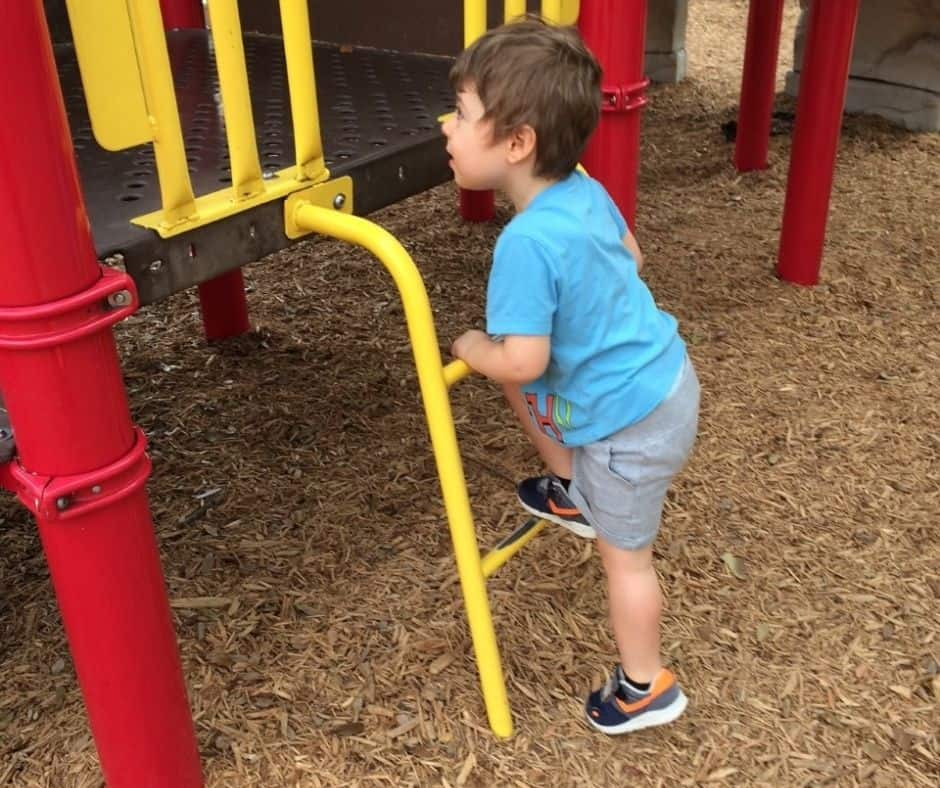 3-year-old climbing up the small ladder on a playground, doing a circuit park activity