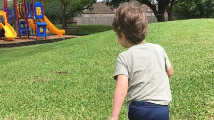 preschooler running towards a playground in a park