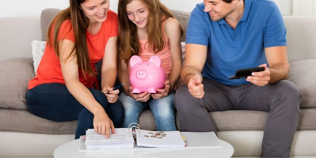 tween with mom and dad and piggybank, tracking their money by paper
