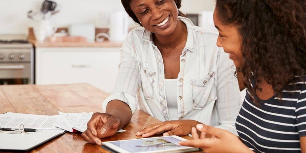 mom with daughter at kitchen table, smiling, teaching teen the value of money